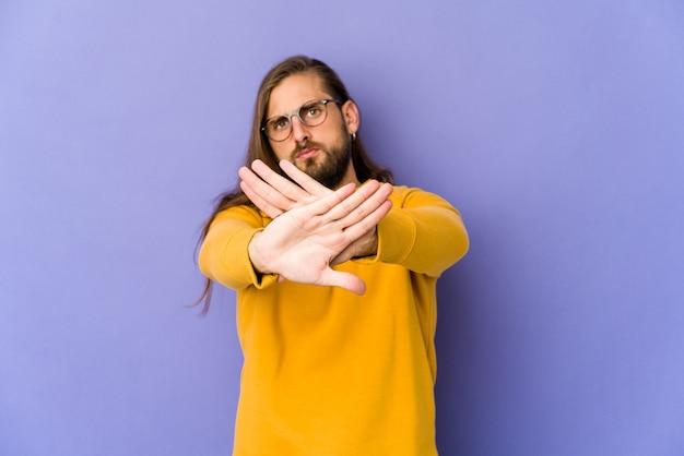 Jovem com cabelo comprido parece em pé com a mão estendida, mostrando o sinal de pare, impedindo você.