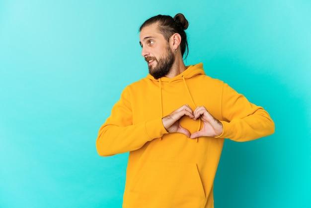 Jovem com cabelo comprido parece sorrindo e mostrando uma forma de coração com as mãos.