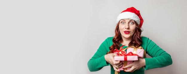 Jovem com cabelo ruivo cacheado, vestindo um chapéu de papai noel vermelho sorrindo e mantém muitas caixas de presentes nas mãos, sobre um fundo cinza