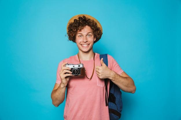 Jovem com cabelos cacheados, vestindo mochila e chapéu de palha fotografando na câmera retro
