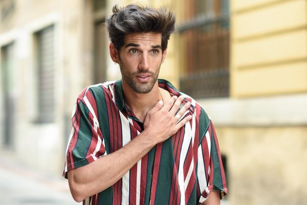 Jovem com cabelos escuros e penteado moderno, vestindo roupas casuais ao ar livre