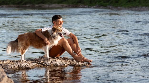 Jovem com cachorro à beira-mar
