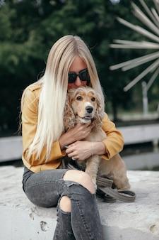 Jovem com cachorro passeios no parque e goza o lindo dia de verão.