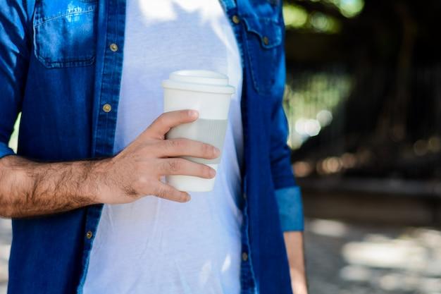 Jovem com café descartável.
