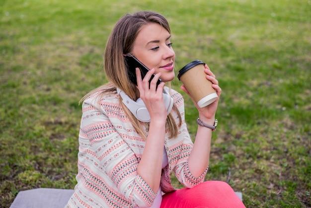 Jovem com café para entrar na mão usando um telefone celular e fones de ouvido no parque. jovem elegante linda garota ouvindo música, telefone celular, fones de ouvido, desfrutando, sorrindo, feliz, acessórios legais, estilo vintage, se divertindo, rir, parque