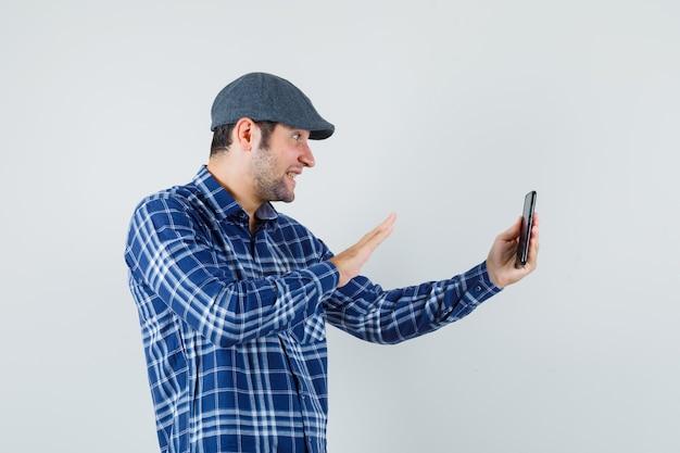 Jovem com camisa, boné acenando com a mão no chat por vídeo e olhando alegre, vista frontal.