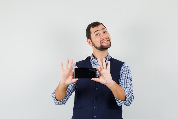 Jovem com camisa, colete tirando foto no celular e parecendo alegre