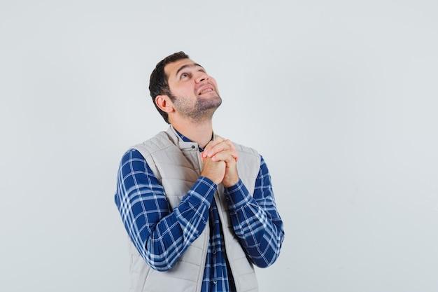 Jovem com camisa, jaqueta sem mangas, orando por algo e parecendo esperançoso, vista frontal.