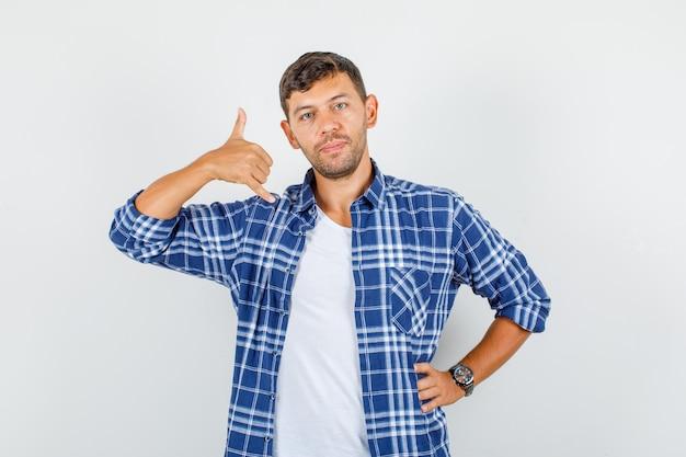 Jovem com camisa, mostrando o gesto do telefone com a mão na cintura e olhando confiante, vista frontal.