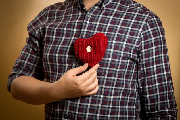 Jovem com camisa posando com coração de malha vermelha