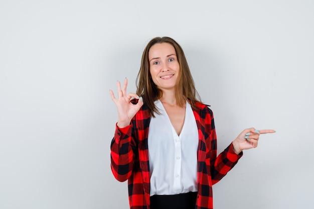 Jovem com camisa quadriculada, blusa mostrando o gesto de ok, apontando para o lado e parecendo feliz, vista frontal.