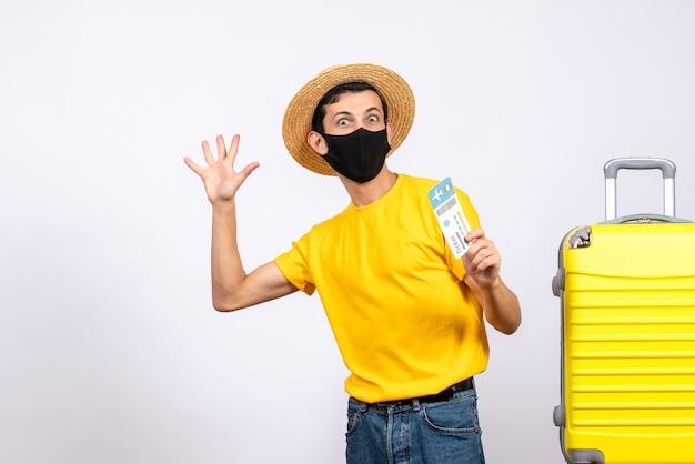 Jovem com camiseta amarela, em pé perto da mala amarela, segurando uma passagem de viagem, acenando com a mão