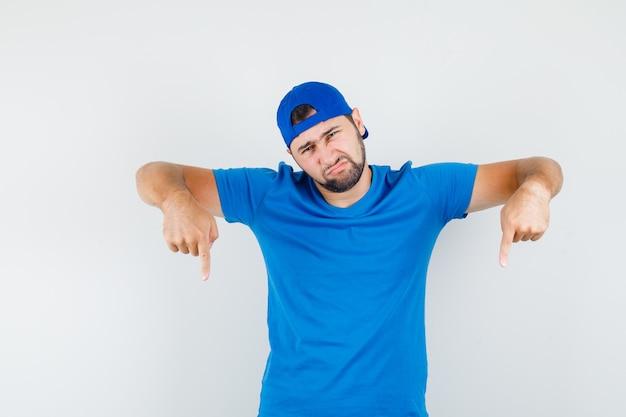 Jovem com camiseta azul e boné apontando para baixo e parecendo desapontado