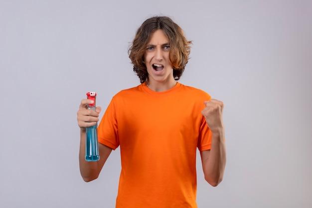 Jovem com camiseta laranja segurando spray de limpeza punho cerrado, regozijando-se com o sucesso e a vitória feliz e saiu de pé sobre um fundo branco