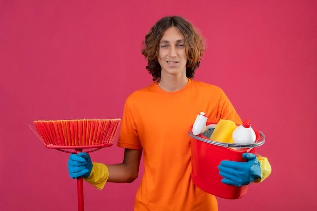 Jovem com camiseta laranja usando luvas de borracha segurando balde com ferramentas de limpeza e esfregão olhando para a câmera sorrindo positivo e feliz em pé sobre fundo rosa