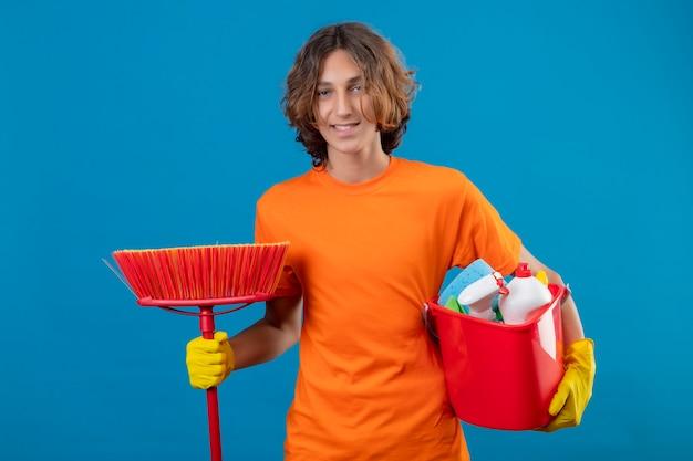 Jovem com camiseta laranja usando luvas de borracha, segurando um balde com ferramentas de limpeza e esfregão olhando para a câmera, sorrindo positivo e feliz em pé sobre um fundo azul