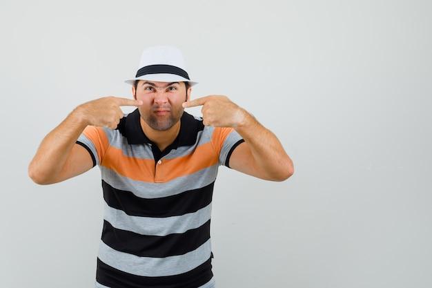 Jovem com camiseta listrada, chapéu apontando para o nariz e parecendo esquisito