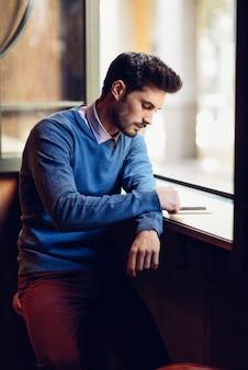 Jovem com camisola azul olhando para o smartphone em um pub moderno.