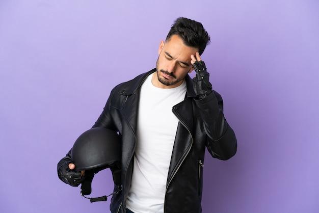 Jovem com capacete de motociclista isolado em fundo roxo com dor de cabeça
