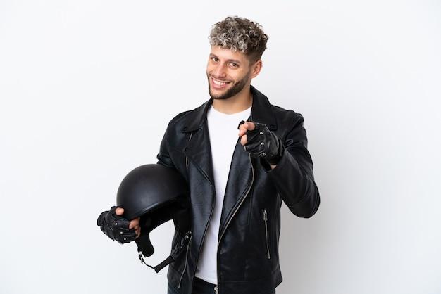 Jovem com capacete de motociclista isolado no fundo branco apontando para a frente com expressão feliz