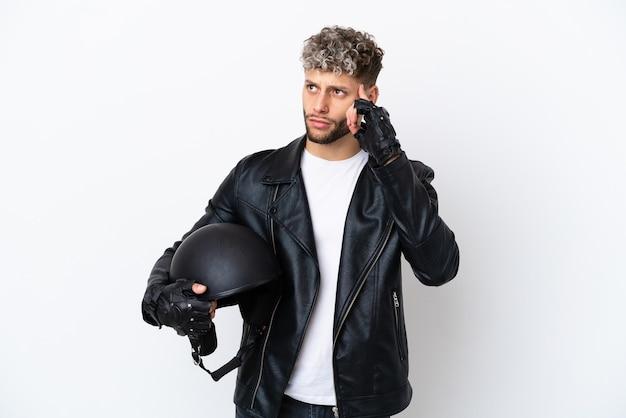 Jovem com capacete de motociclista isolado no fundo branco, tendo dúvidas e pensando