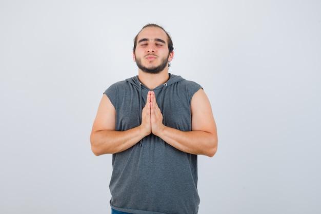 Jovem com capuz, mostrando o gesto namastê e olhando relaxado, vista frontal.