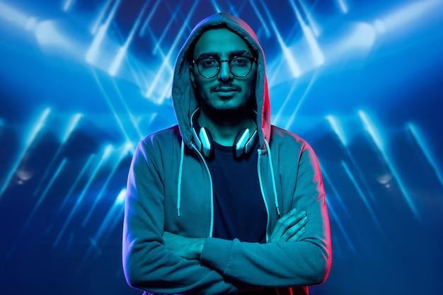 Jovem com capuz, óculos e camiseta cruzando os braços sobre o peito em pé sob as luzes azuis
