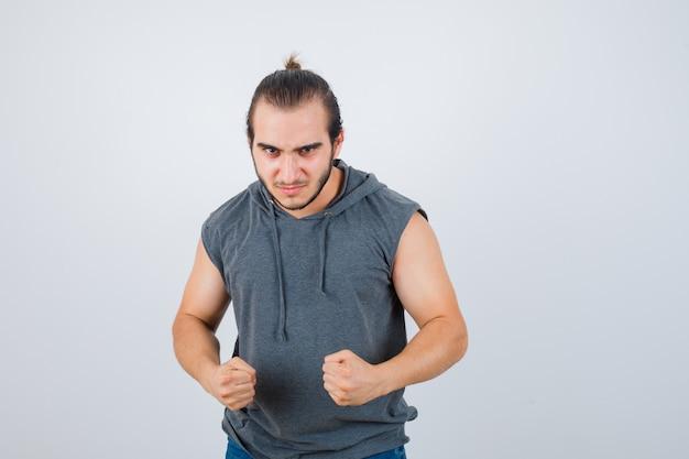 Jovem com capuz sem mangas em pé em pose de luta e olhando rancoroso, vista frontal.