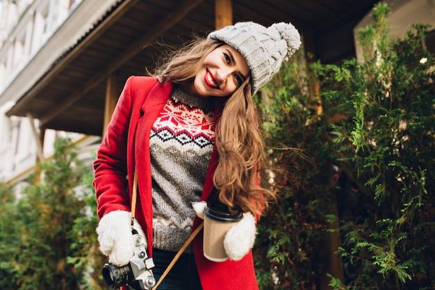 Jovem com casaco vermelho, andando na rua com café para ir. ela usa luvas brancas, sorrindo.