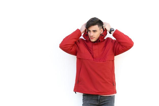 Jovem com casaco vermelho sobre parede branca