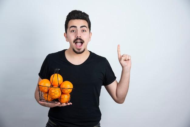 Jovem com cesta metálica cheia de frutas laranja apontando para cima.