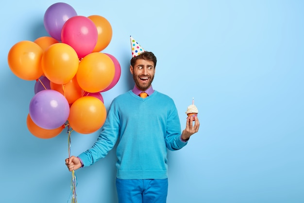 Jovem com chapéu de aniversário e balões posando com um suéter azul