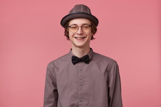 Jovem com chapéu de camisa e gravata borboleta preta usa óculos bem sorrindo, mostrando os suportes ortodônticos isolados em um fundo rosa
