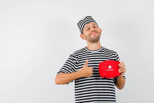 Jovem com chapéu de camiseta listrada segurando um kit de primeiros socorros, mostrando o polegar e parecendo alegre