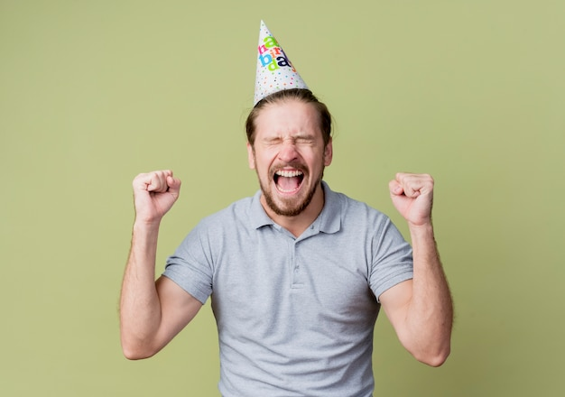 Jovem com chapéu de feriado comemorando aniversário feliz e animado com a parede de luz