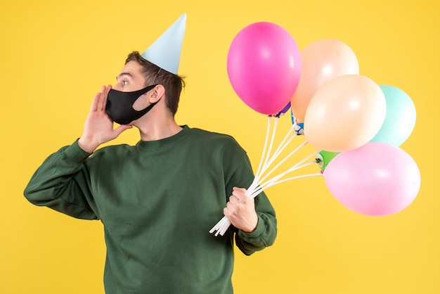 Jovem com chapéu de festa e balões coloridos chamando alguém de pé no amarelo