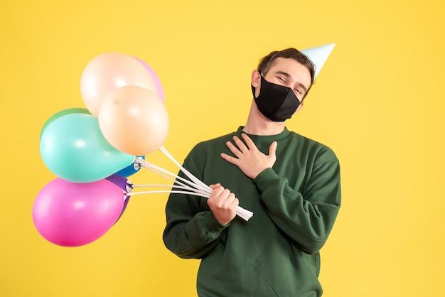 Jovem com chapéu de festa e balões coloridos colocando a mão no peito em amarelo