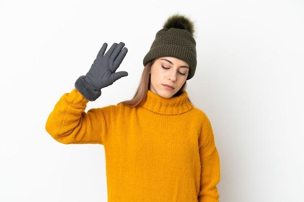 Jovem com chapéu de inverno isolada no fundo branco fazendo gesto de pare e decepcionada