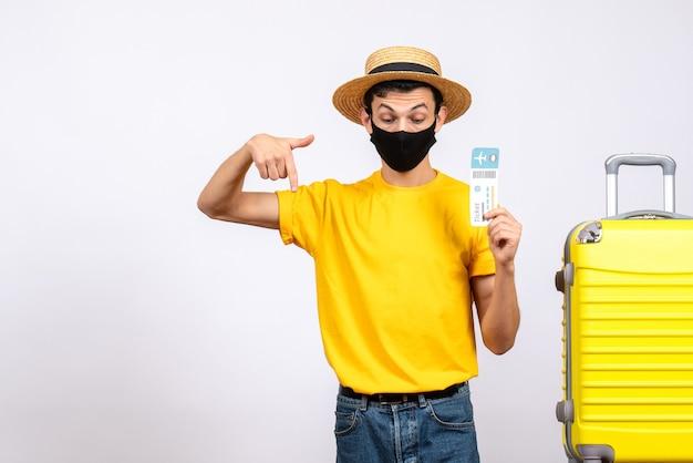 Jovem com chapéu de palha e máscara em pé perto da mala amarela segurando uma passagem de viagem apontando para baixo
