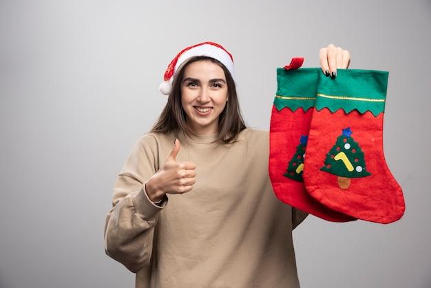 Jovem com chapéu de papai noel aparecendo um polegar e segurando duas meias de natal.