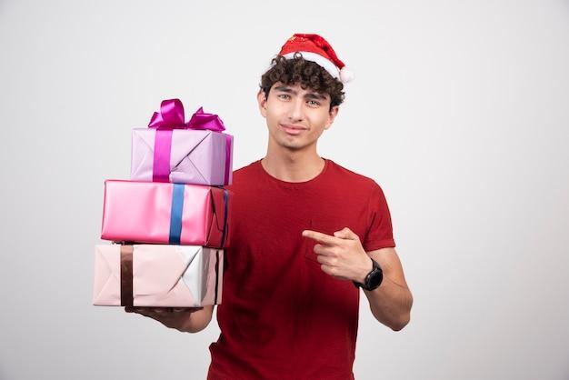 Jovem com chapéu de papai noel, apontando para caixas de presente.