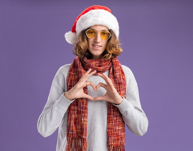 Jovem com chapéu de papai noel de natal e óculos amarelos com lenço quente no pescoço, sorrindo, fazendo gesto de coração com as mãos e os dedos em pé sobre a parede roxa