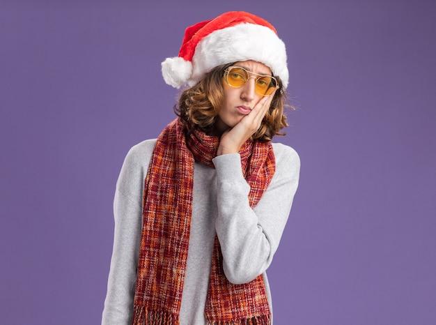Jovem com chapéu de papai noel de natal e óculos amarelos com um lenço quente em volta do pescoço confuso com a mão no rosto em pé sobre a parede roxa