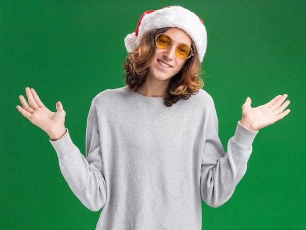 Jovem com chapéu de papai noel de natal e óculos amarelos, olhando para a câmera com um sorriso no rosto, estendendo os braços para os lados em pé sobre um fundo verde