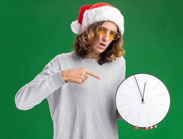 Jovem com chapéu de papai noel de natal e óculos amarelos segurando um relógio de parede apontando com o dedo indicador para ele, parecendo confuso em pé sobre uma parede verde