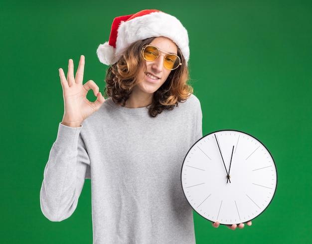 Jovem com chapéu de papai noel de natal e óculos amarelos segurando um relógio de parede e sorrindo mostrando uma placa de ok em pé sobre a parede verde