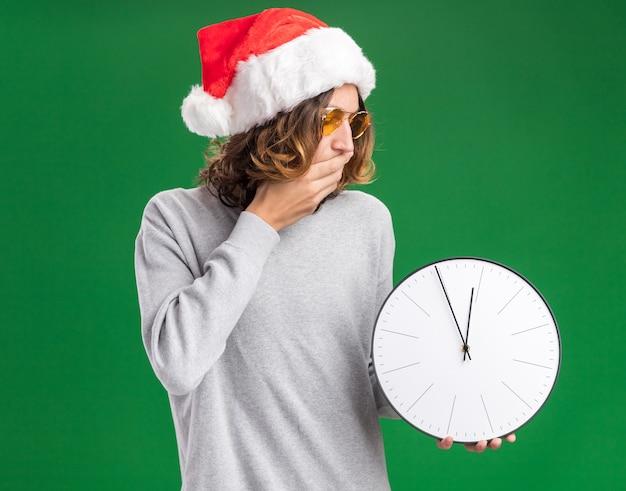 Jovem com chapéu de papai noel de natal e óculos amarelos segurando um relógio de parede, olhando para ele espantado, cobrindo a boca com a mão em pé sobre a parede verde