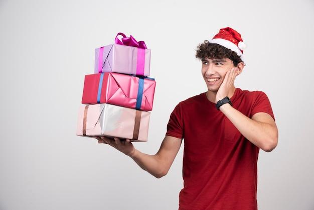 Jovem com chapéu de papai noel olhando para presentes alegremente.