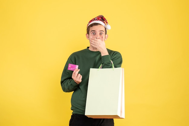 Jovem com chapéu de papai noel segurando sacolas de compras e cartão colocando a mão na boca sobre fundo amarelo
