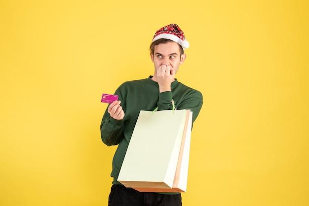 Jovem com chapéu de papai noel segurando sacolas de compras e cartão de crédito em pé sobre fundo amarelo.